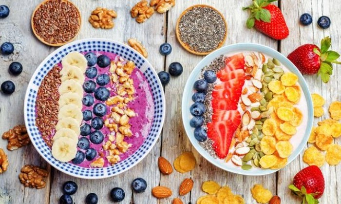 two bowls with pink and white yoghurt, topped with various seeds, cornflakes and almonds, banana slices and blueberries, strawberries and walnuts