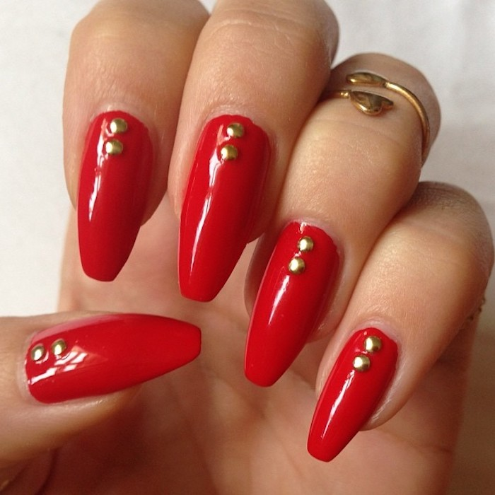 classic red nail polish, on a hand seen in close up, with coffin shaped nails, each nail is decorated with two gold rhinestones