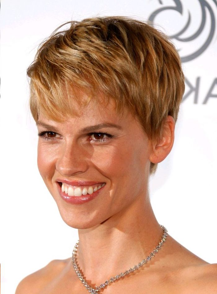 short textured pixie cut, on brunette hair with honey blonde highlights, short haircuts for thin hair, worn by smiling hilary swank