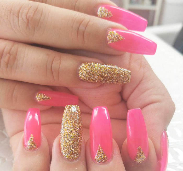 triangles made of gold glitter, decorating the long hot pink squoval nails, of two hands, both ring finger nails are entirely covered in gold glitter