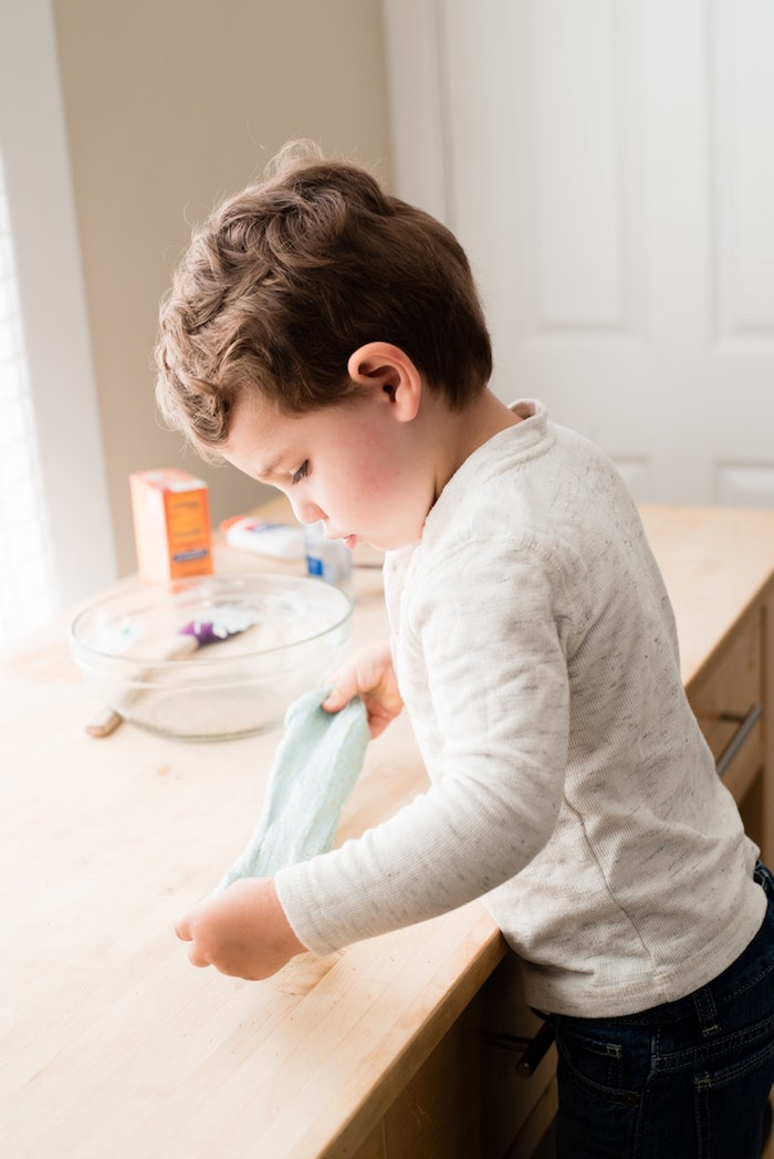little boy stretching a piece of light blue goo, over a light wooden desk, clear glass bowl, spatula and ingredients nearby, fluffy slime recipe