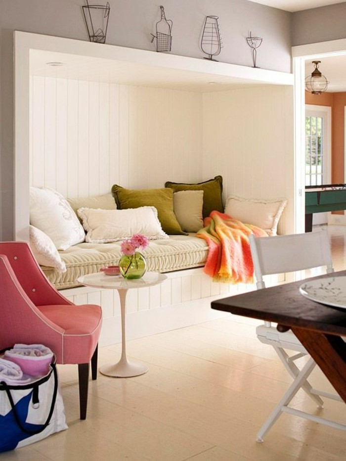 sitting nook inbuilt in a wall, with white wooden paneling, and several different pillows, in white and green, pink armchair and a small white coffee table, room design