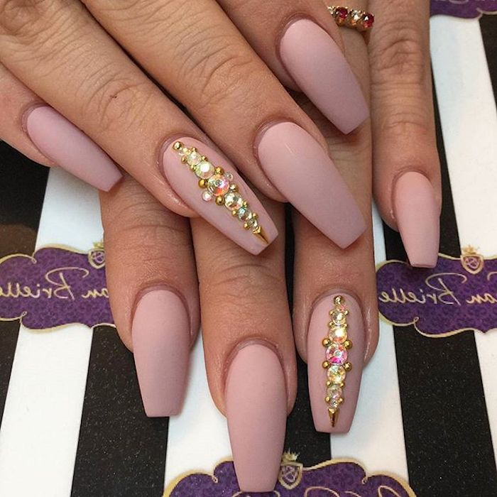 ring finger nails decorated with rhinestones, on two hands with long, nude coffin nails, in a pinky beige shade