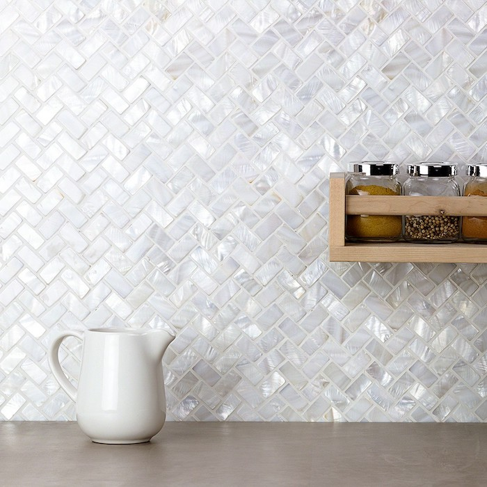 pearlescent white tiles, on a herringbone backsplash, near a beige counter top, with a white milk jug, and a wooden shelf, with condiment jars