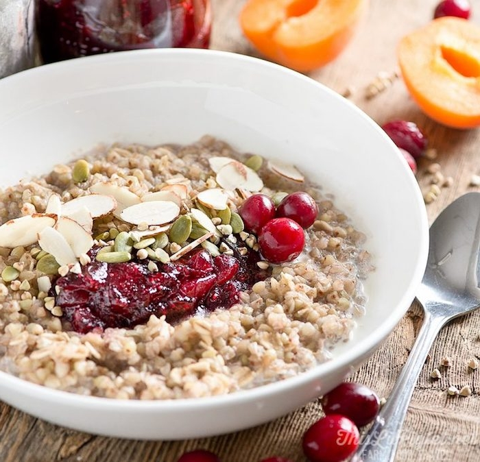 buckwheat mash inside a white ceramic bowl, topped with fresh cranberries and cranberry sauce, pumpkin seeds and almonds, healthy breakfast ideas, metal spoon nearby