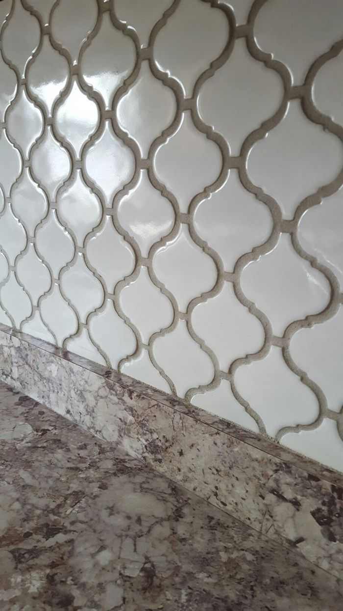 extreme close up of an arabesque tile backsplash, in milky white, with beige joints, near a spotty beige, smooth counter top