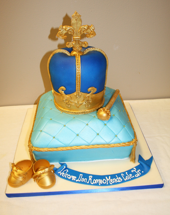 crown made from dark blue, and gold fondant, on top of a cake shaped like a pillow, in light blue and gold, with tiny gold shoes, and a blue ribbon, with white writing