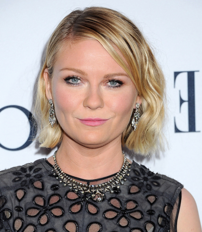 pewter grey top, with flower-shaped cutouts, worn by kirsten dunst, with short slightly wavy bob, side part and dark blonde roots, short haircuts for fine hair