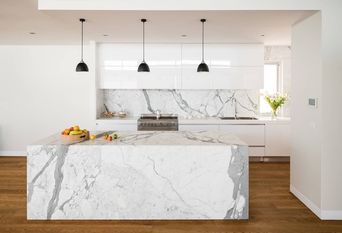 floor covered in brown laminate, under a marble kitchen island, in white and pale grey, with a matching backsplash, smooth white cabinets