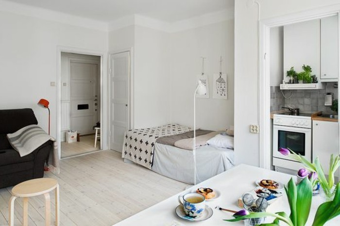 open door in a room with white walls, and a pale beige laminate floor, bed and a black sofa, dining table in white, with flowers and food
