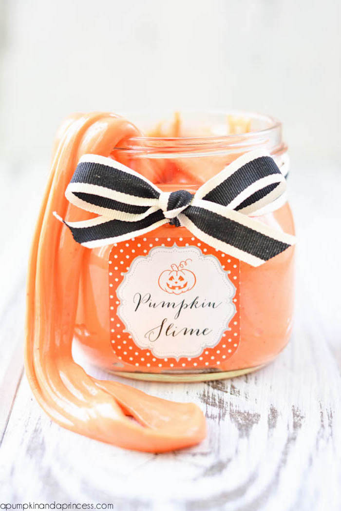 pumpkin slime in orange, inside a small clear jar, with orange and white label, and a black and white ribbon, tied in a bow, slime recipe without borax, light wooden surface