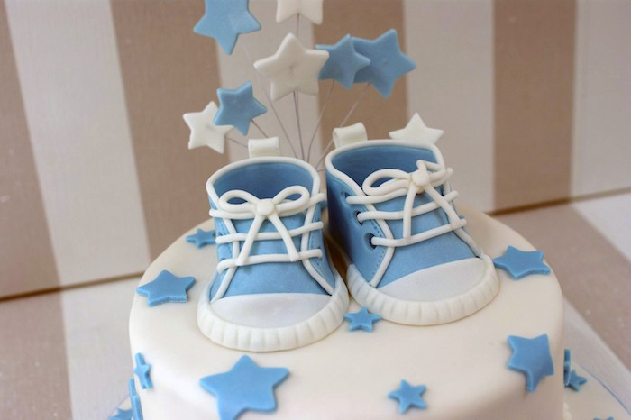 sneakers in pale blue and white, made from fondant, on top of a white cake, with smooth frosting, and pale blue stars, baby shower cakes for boys, star-shaped toppers