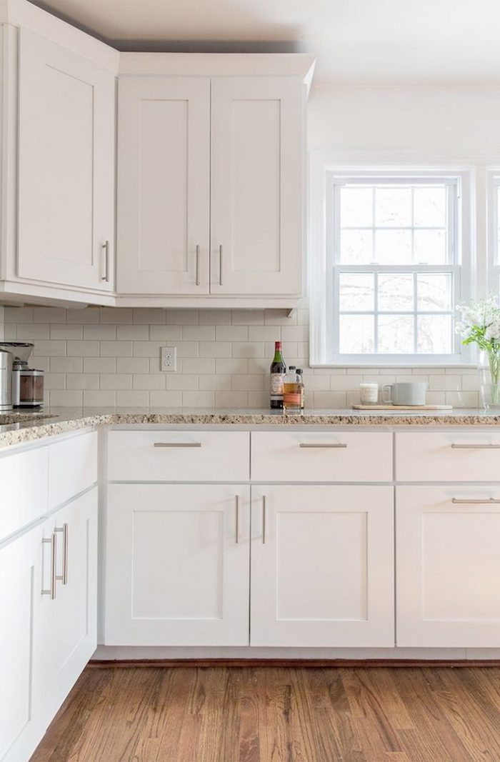 white subway tile pattern, inside a bright kitchen, with brown laminate floor, white cabinets and beige marble counter tops