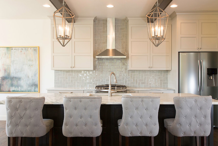 candle-shaped lights, inside two metal lanterns, hanging from the ceiling of a kitchen, marble counter top, pale grey herringbone backsplash
