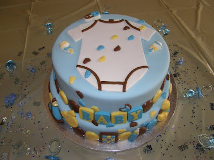 footprints in yellow, brown and blue, decorating a layered light blue cake, topped with a white onesie shape, made from fondant, onesie cake, yellow and blue blocks, spelling out the word baby