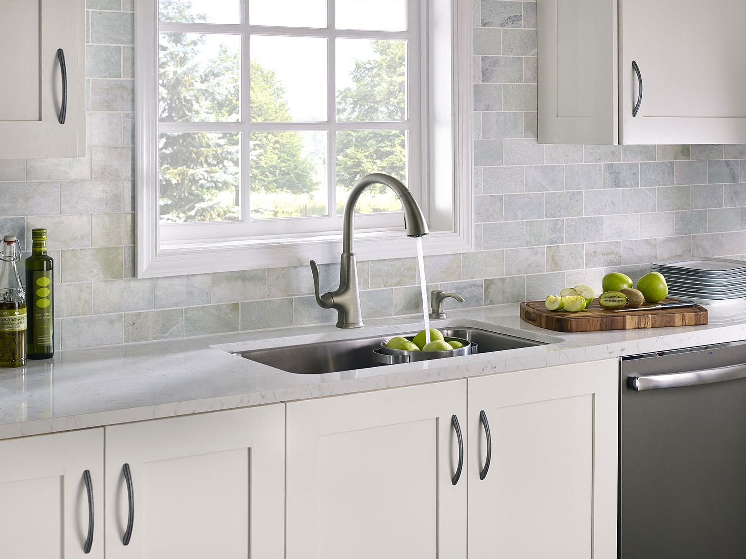 fancy countertops in kitchen in pale tones, with white cupboards, and a metal sink, pale blue brick wall with window, green apples and kiwis