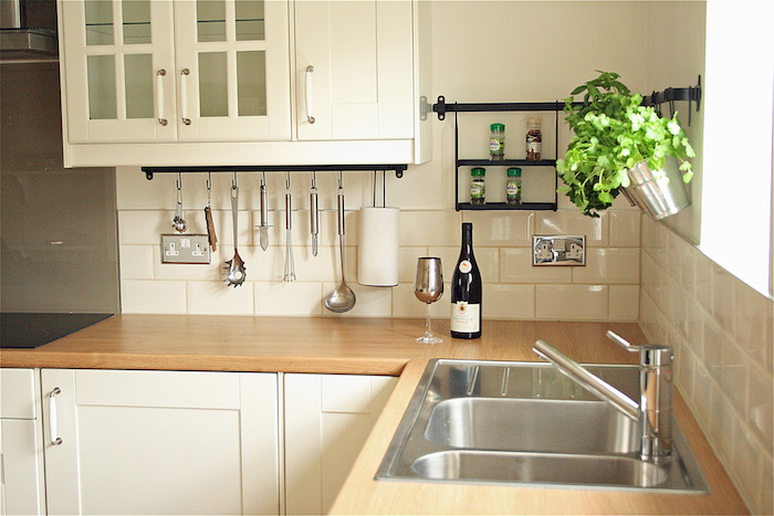 counter tops made from wood, in a light color, with an inbuilt metal sink, and white cabinets, white subway tile pattern on the walls