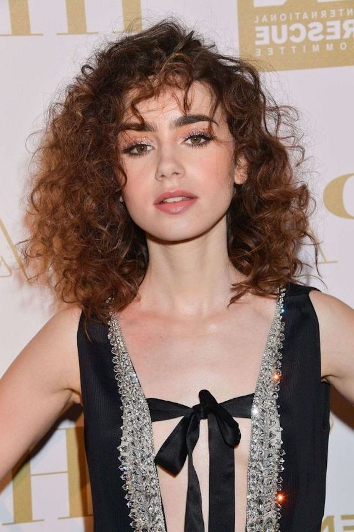 actress lily collins, wearing a fancy, black sequined dress, with ribbon detail, messy shoulder-length hair, hairstyles for short curly hair, with curly bangs