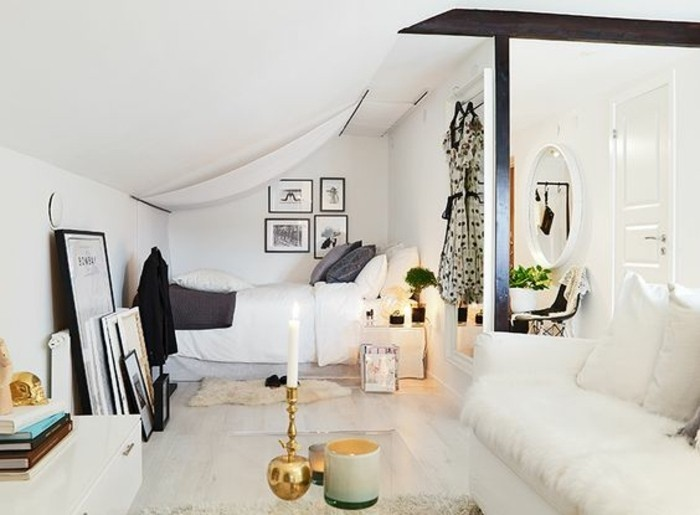 stacks of books, and framed artworks, propped up on a wall, inside a small studio in white, room setup ideas, white sofa and clear glass coffee table