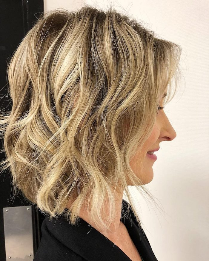 beach waves on a long, dark ash blonde bob, with light blonde balayage, on a woman in profile, medium length hairstyles for thin hair, wearing a black top