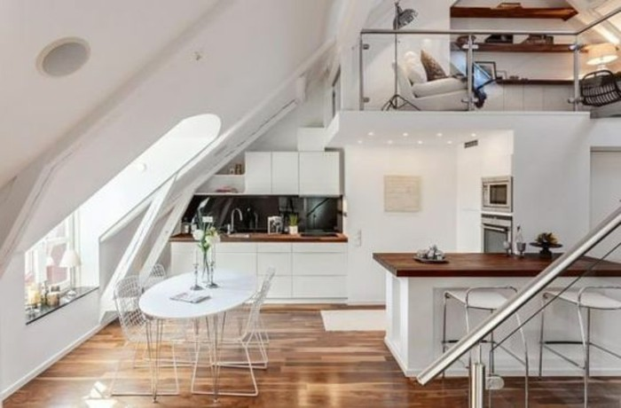 oval dining table in white, and four chairs, inside a loft studio flat, with brown laminate floor, kitchenette and an upper level, with a sitting area