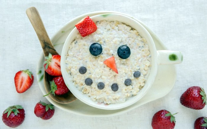 smily face created with fruit, blueberries and strawberry slices, on top of a porridge, inside a large ceramic mug, healthy low calorie breakfast, wooden spoon and whole strawberries