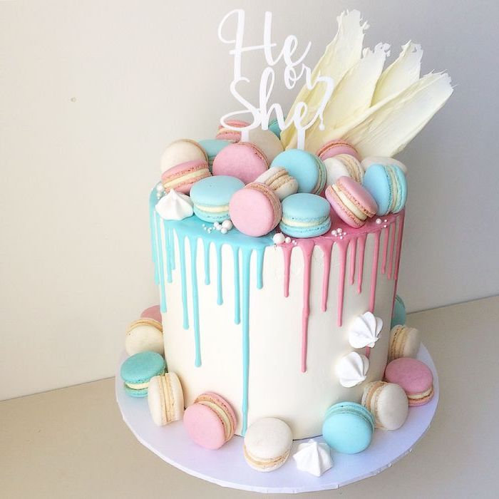 he or she written on a white cake topper, placed on a tall cake, with smooth white frosting, decorated with pink, blue and white macaroons
