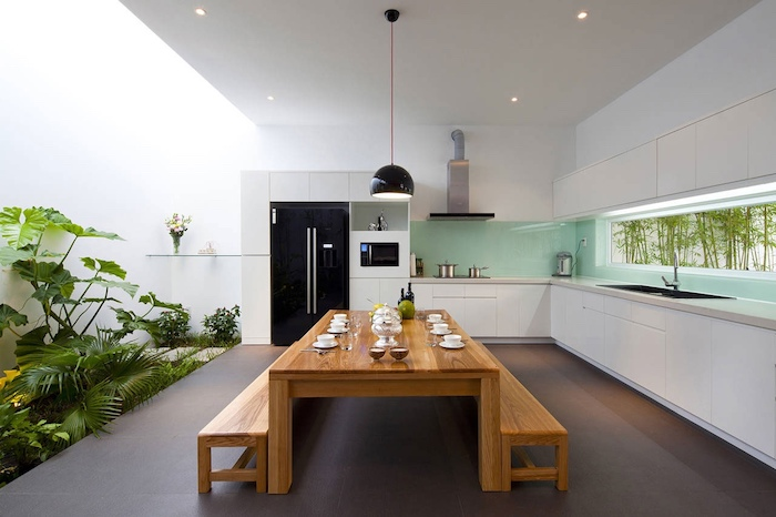 lots of green vegetation, in a large room, with white walls, and a smooth grey floor, long wooden dining table, with two matching benches, turquoise glass backsplash
