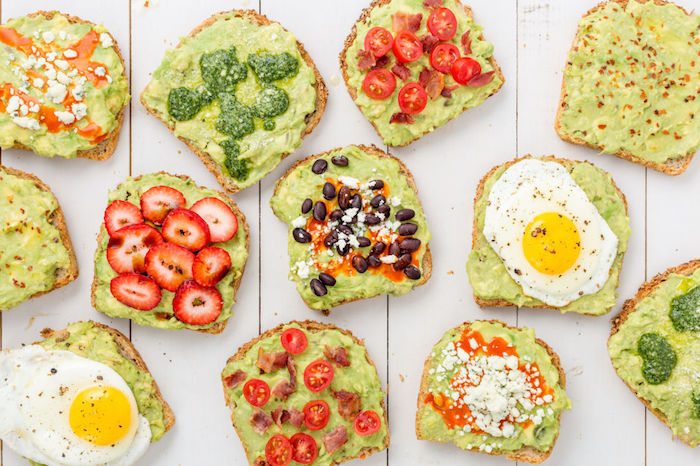 best breakfast for weight loss, twelve pieces of toast, with guacamole spread, and different toppings, strawberries and eggs, cherry tomatoes and beans