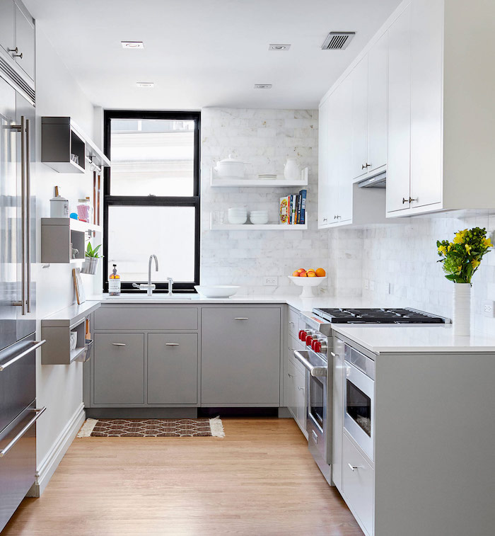laminate floor in a small kitchen, with pale grey and white cabinets, light marble subway tile kitchen backsplash, and a slide up window