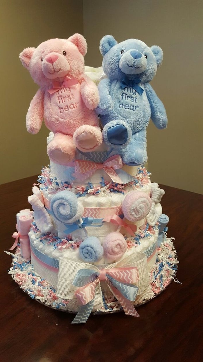 stuffed teddy bears, in pale pink and blue, with the words my first teddy, embroidered on their tummies, topping a diaper cake in pastel colors, twin baby shower cakes