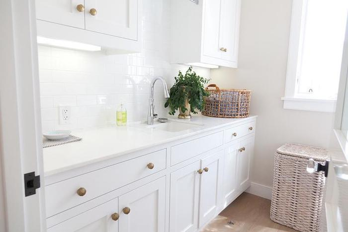 pure white subway tile pattern, glossy kitchen back splash, in a room with white cabinets, beige floor and a sink, large and small wicker baskets