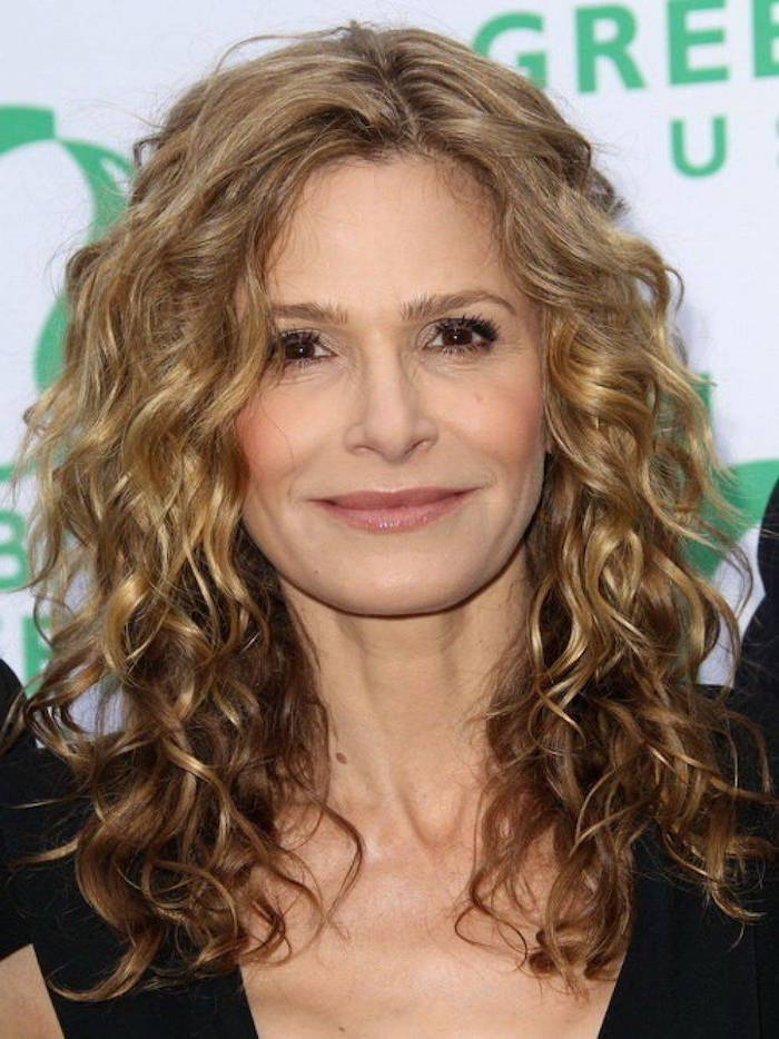 balayage on shoulder-length curly hair, blonde with light brunette tips, curly haircuts, worn by smiling mature woman, in a black top