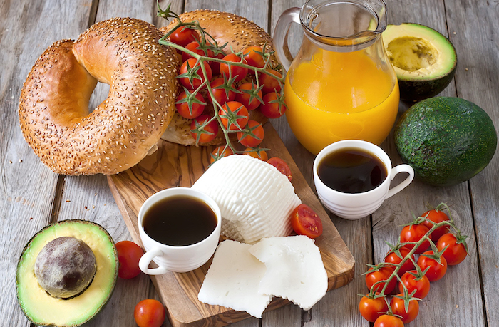 white cheese and cherry tomatoes on the vine, near avocados and bread, on a wooden table with a cutting board, low calorie breakfast, orange juice and two cups of coffee
