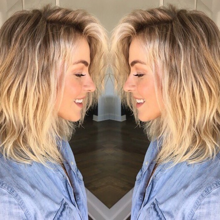 mirrored image of a smiling blonde woman, wearing a messy long bob, with dark roots, medium length hairstyles for thin hair, light denim shirt