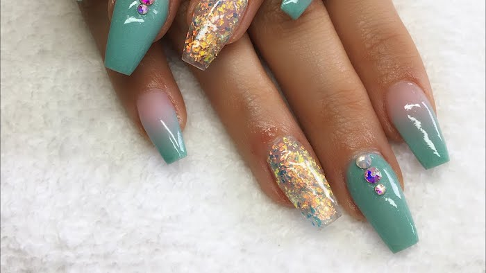 turquoise coffin acrylic nails, decorated with pale pink, gold and blue glitter, and rhinestones in white, purple and iridescent silver
