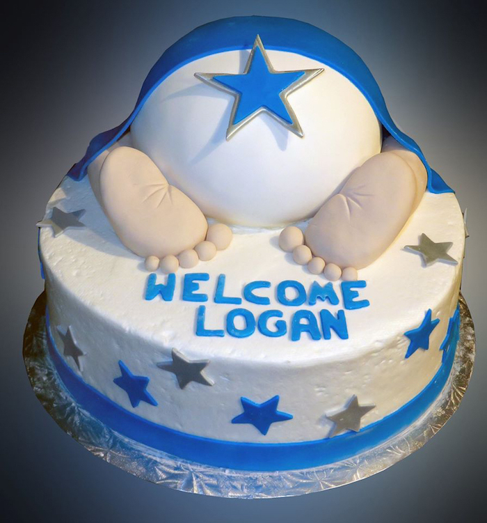 feet and nappy made from fondant, under a blue fondant blanket, topping a white cake, with a festive message, and blue and silver stars