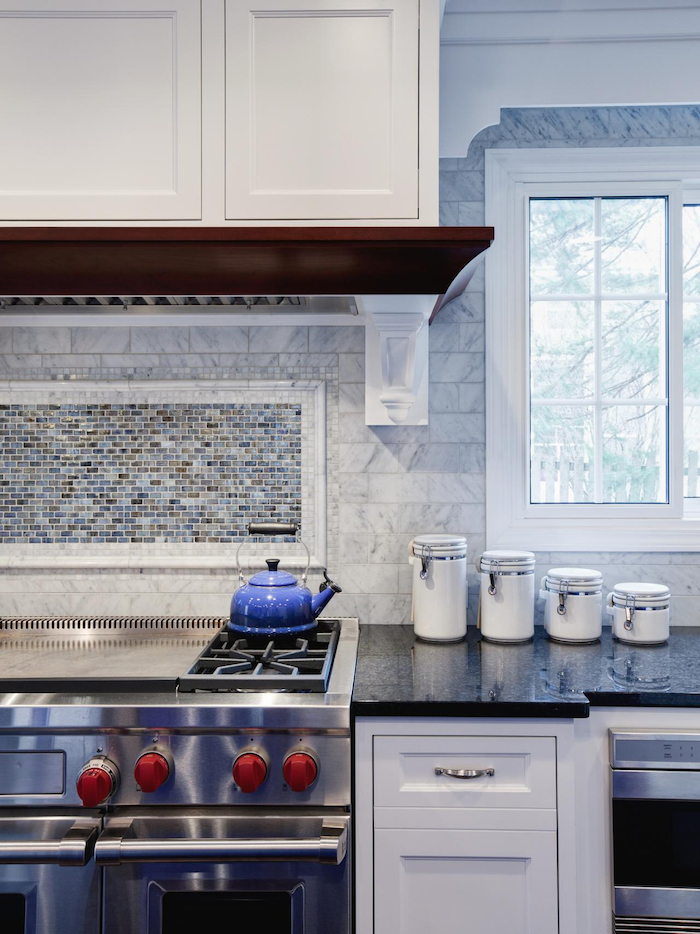 teapot in a vivid blue color, on a metal hob, near a dark counter top, and a pale grey, subway tile kitchen backsplash, with a marble pattern