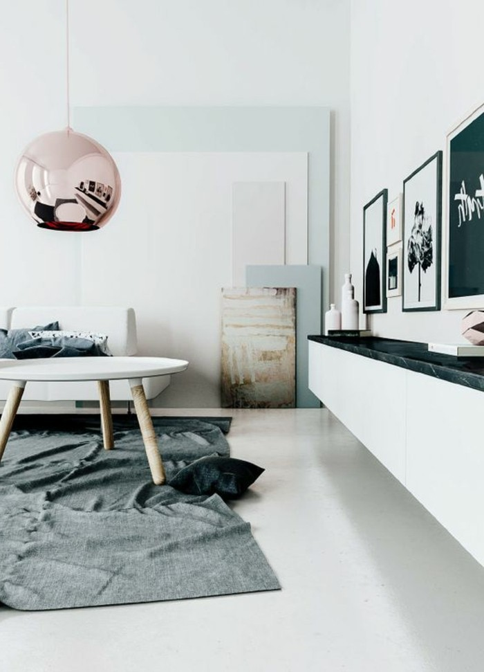 room setup ideas, round metallic lamp in pink, hanging above a white coffee table, inside a white room, with grey rug, and several framed artworks