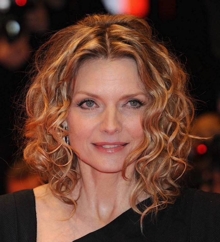 honey blonde hair, curly with middle part, worn by michelle pfeiffer, in a black asymmetric top, short haircuts for curly hair, subtle minimalistic make up