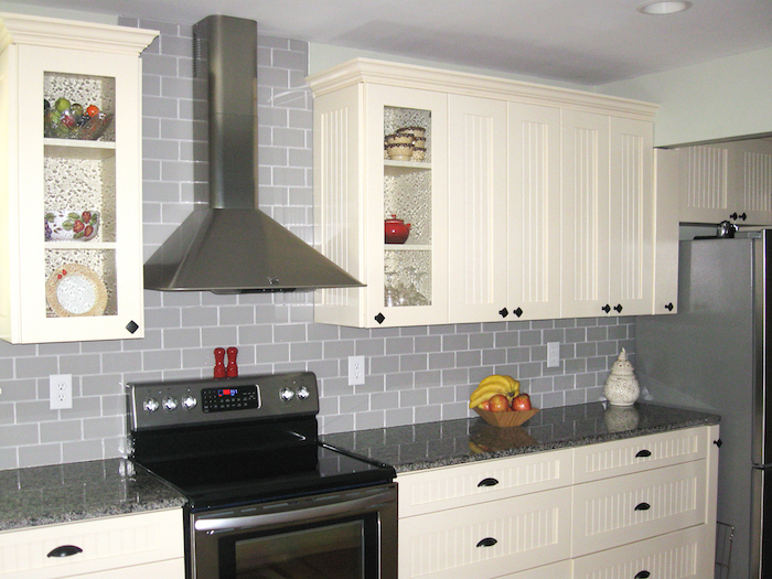 bowl of fruit, on a glossy grey counter top, near a wall, with creamy grey subway tile pattern, white kitchen cabinets