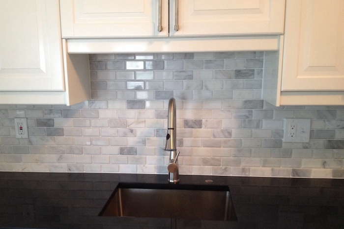 small sink with a metal faucet, in a smooth black counter top, near pale grey subway tile wall, with white kitchen cabinets