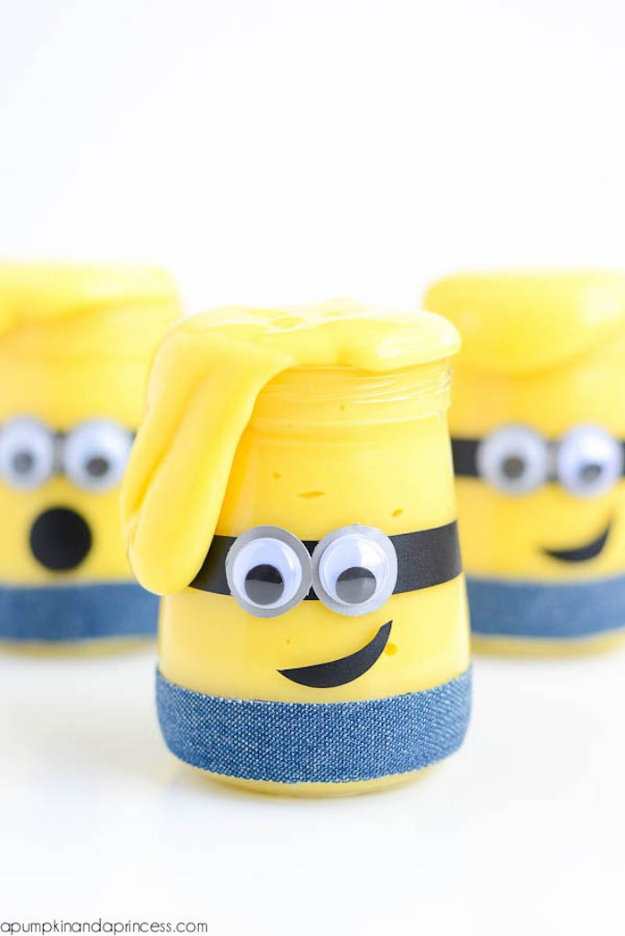 three minions made from yellow goo, stuck in small jars, slime recipe without borax, decorated with denim-colored washi tape, black paper cutouts, and googly eye stickers