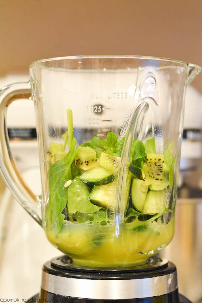 cucumber chunks and kiwi slices, spinach and mint leaves, inside the jug of a blender, healthy breakfast ideas, some yellow juice