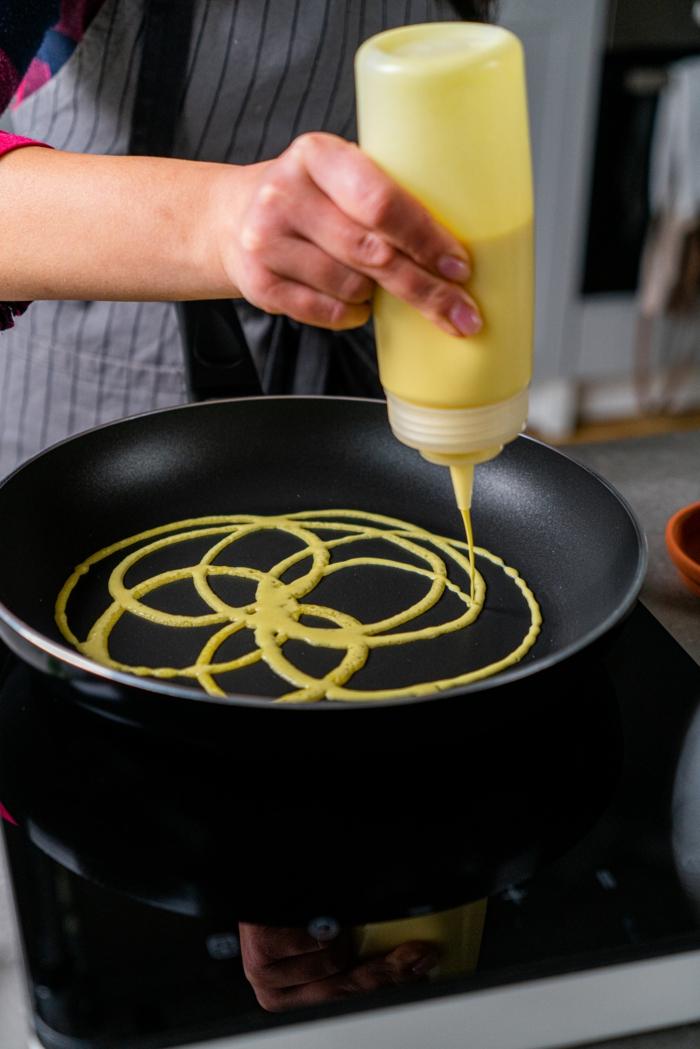 net pancakes recipe, pancakes mixture poured into black pan, plastic bottle