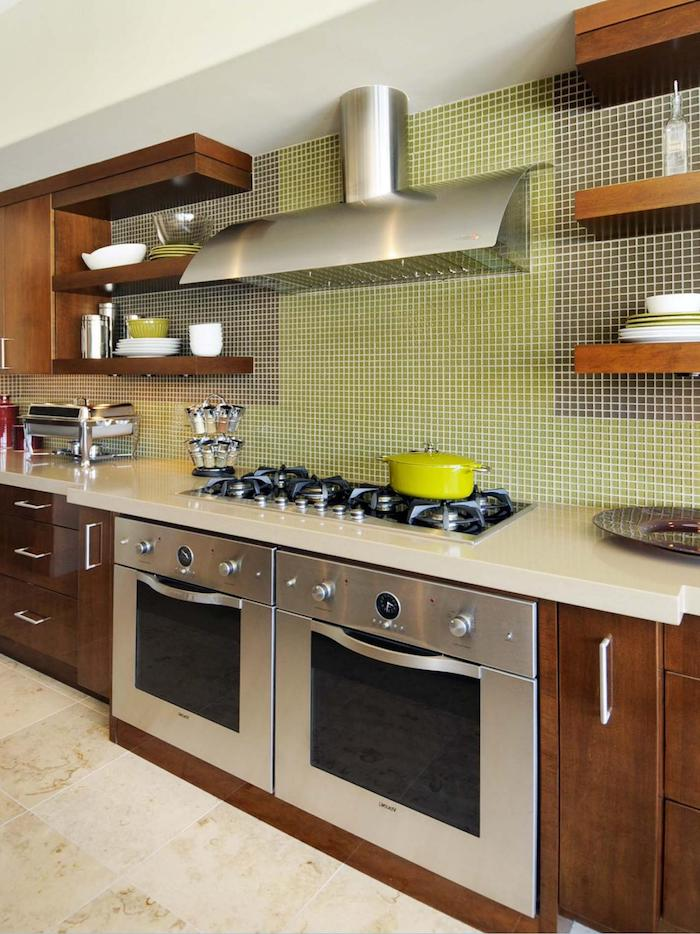 brown wooden cabinets, and a pale cream counter top, in a kitchen with two ovens, light beige tiled floor, and a green and grey mosaic on the wall
