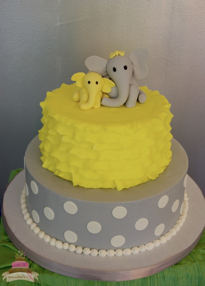 child and mother elephant, made from yellow and grey fondant, topping a grey and yellow elephant baby shower cake, decorated with frills and white polka dots