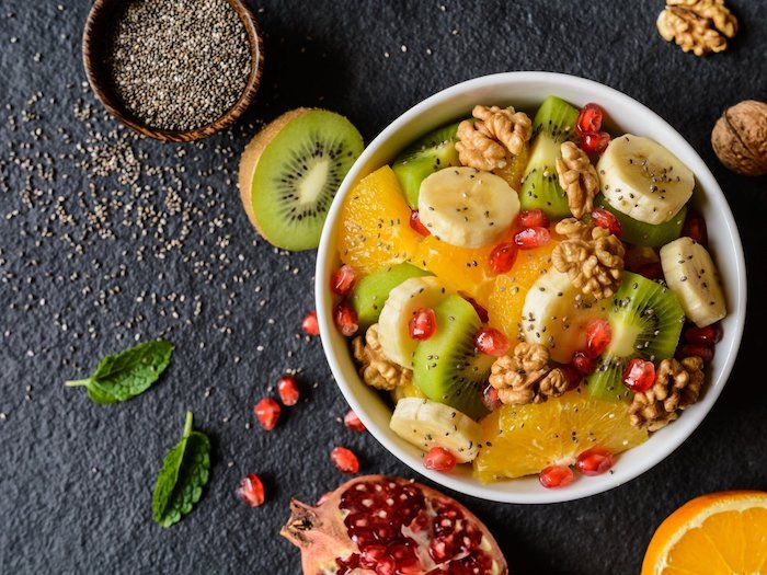 healthy breakfast ideas, white ceramic bowl, filled with slices of fruit, orange and kiwi, banana and pomegranate seeds, and topped with walnuts