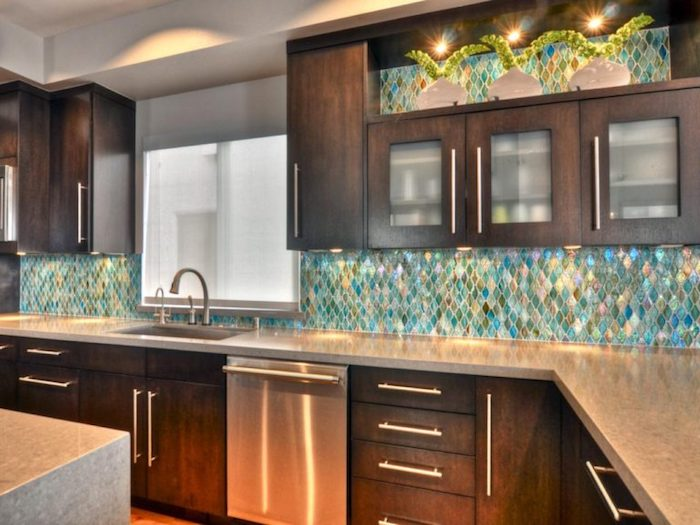 fish scale effect wall, in iridescent turquoise, green and pink, inside a kitchen, with dark brown wooden cabinets, and light grey counter tops