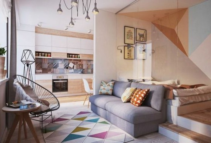 hanging lights inside a studio flat, with a multicolored rug, a grey sofa and a bed, a kitchenette and some framed artworks